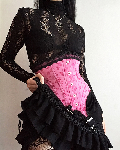 Front view of the pink edwardian corset paired with a short black ruffled skirt