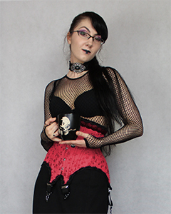 Aranea Black wearing a gothic outfit with a red underbust corset and a black coffee cup