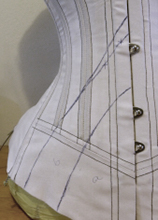 Vertical seam victorian corset mock up with first design lines drawn on the bottom
