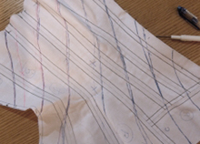 Corset mock up with diagonal lines drawn on laying flat on table ready for cutting