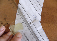 Straightening the crooked corset pattern piece to prepare it for tracing on to paper