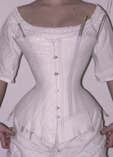 Front side of vertical Victorian corset and diagonal seam corset mock up halves worn together for testing