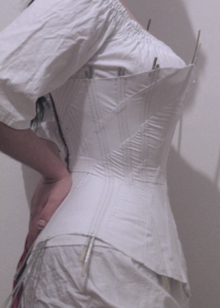 Side view of diagonal seam corset mock up halves worn together for testing